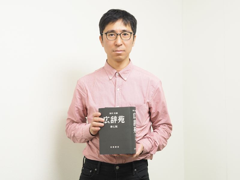 広辞苑を持つ編集部平木さん